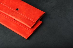 A pair of red genuine leather wallets with rivets on a dark background top view. Genuine leather