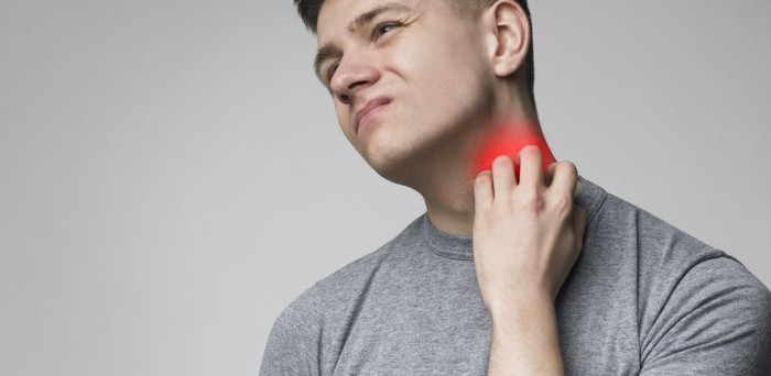 Young man scratching his itchy neck with allergy rash